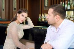 L'homme et la femme regardent l'un l'autre la fille et le type s'asseyent dans la barre, restaurant image libre de droits