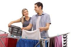 L'homme et la femme reprenant vêtx du dessiccateur de support image stock
