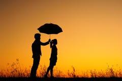 L'homme et la femme retiennent le parapluie en coucher du soleil de soirée Photographie stock libre de droits