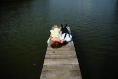 L'homme et la femme s'étendent sur le pont sur le lac Photos libres de droits