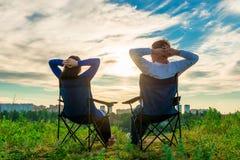 L'homme et la femme s'asseyant dans les chaises et admirent le lever de soleil Photos stock
