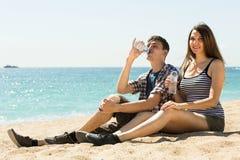 L'homme et la femme s'asseyant sur le sable et la boisson arrosent Photographie stock libre de droits