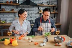 L'homme et la femme s'asseyent ensemble à la table dans la cuisine Ils préparent le dîner ensemble Tomate et regard de coupe de f image libre de droits