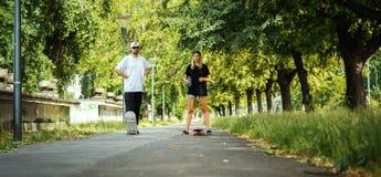 L'homme et la femme se tiennent avec des planches à roulettes sur la rue Photographie stock