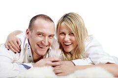 L'homme et la femme se trouvent sur le tapis et le rire Photo stock