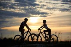L'homme et la femme sur des bicyclettes se tiennent à la route vis-à-vis de l'un l'autre et regardent pour dégrossir coucher du s Image stock