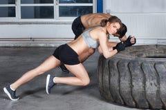 L'homme et la femme sur une formation de forme physique de crossfit de pneu réchauffent image libre de droits