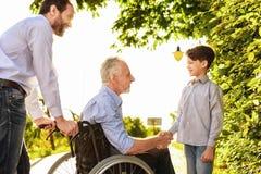L'homme et le garçon sont venus au parc pour voir leur grand-père, qui s'assied sur un fauteuil roulant en parc Photo libre de droits