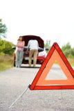 L'homme et les femmes adultes s'approchent de la voiture cassée image stock