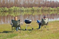 L'homme et les femmes s'asseyent sur un rivage de rivière et font le barbecu Photographie stock libre de droits