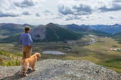 L'homme et son chien admirent le paysage de montagne Image libre de droits