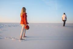L'homme et une jeune belle femme entrent un dans le désert Photographie stock libre de droits