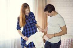 L'homme et une jeune femme enceinte attendent un enfant à la maison b Photo libre de droits