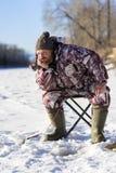 L'homme européen barbu ennuyeux tandis qu'il pêchant du trou de glace image libre de droits