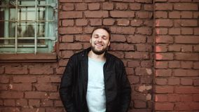 L'homme européen bel enthousiaste sourit dans l'appareil-photo L'homme d'affaires masculin réussi heureux se tient près du mur de banque de vidéos