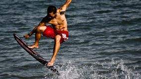L'homme exécute des tours sur sa planche de surf photographie stock