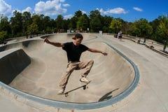 L'homme exécute le tour d'entre le ciel et la terre dans la cuvette au parc de planche à roulettes Photos libres de droits