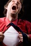 L'homme exaspéré déchire hors fonction une chemise rouge Photographie stock libre de droits