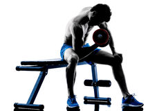 L'homme exerçant la forme physique pèse la silhouette d'exercices de banc à presse Photographie stock libre de droits