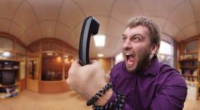 L'homme fâché parle du téléphone photographie stock libre de droits