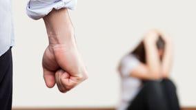 L'homme fâché a soulevé le poing au-dessus de la femme s'asseyante faisante le coin de mur image stock