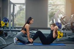 L'homme faisant des craquements abdominaux pressent l'exercice avec l'entraîneur personnel féminin photo libre de droits