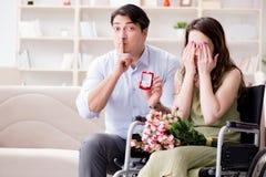 L'homme faisant la proposition de mariage à la femme handicapée sur le fauteuil roulant Images libres de droits