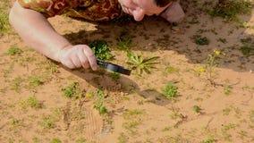 L'homme fait l'analyse visuelle soigneuse de l'empreinte de pas sur le sable avec la loupe banque de vidéos