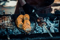 L'homme fait cuire sur le maïs et la viande de barbecue photos libres de droits