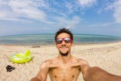 L'homme fait le selfie sur les roches par la mer Image libre de droits