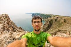 L'homme fait le selfie sur les roches par la mer Images libres de droits