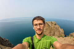 L'homme fait le selfie sur les roches par la mer Photo stock