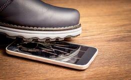 L'homme a fait un pas à un téléphone portable et a endommagé le verre Phone_ mobile entaillé images stock