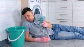 L'homme fatigué dans les gants en caoutchouc a un repos du nettoyage s'étendant sur le plancher de cuisine banque de vidéos