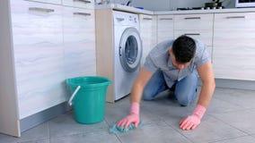 L'homme fatigué malheureux dans les gants en caoutchouc lave le plancher dans la cuisine et des regards à la caméra à l'extrémité clips vidéos
