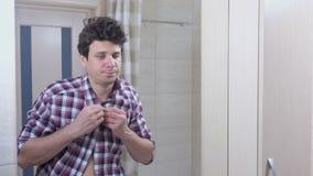 L'homme fatigué somnolent avec des bâillements d'une gueule de bois pendant le matin dans la salle de bains attache sa chemise et banque de vidéos
