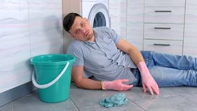 L'homme fatigu? dans les gants en caoutchouc a un repos du nettoyage s'?tendant sur le plancher de cuisine banque de vidéos
