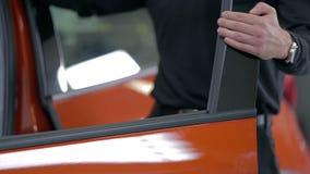 L'homme ferme la porte d'une voiture rouge clips vidéos