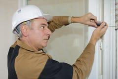 L'homme fixe des abat-jour de base pour encadrer la fenêtre images libres de droits