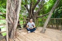 L'homme font la méditation sur la cabane dans un arbre photographie stock libre de droits