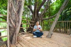 L'homme font la méditation sur la cabane dans un arbre images libres de droits