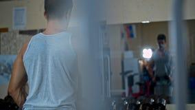 L'homme forme le biceps et les bras muscle sur le périphérique en mode bloc banque de vidéos