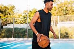 L'homme fort bel tient la boule sur le terrain de basket Homme avec une boule, équipement de sport Images stock