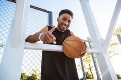 L'homme fort bel tient la boule sur le terrain de basket Homme avec une boule, équipement de sport, compétitions sportives Images libres de droits