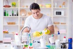 L'homme frustré à devoir laver des plats images stock