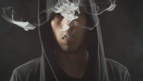 L'homme fume la cigarette électronique et et fait des nuages de fumée, type stylo vaping, d'e-clope et de vape clips vidéos