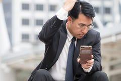 L'homme futé d'affaires regarde son téléphone portable et vérifie son rea Image stock