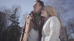 L'homme grand étreint la femme blonde assez jeune dans la veste chaude regardant le haut bâtiment Les couples discutant le pointa banque de vidéos