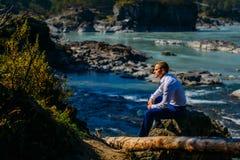 L'homme a habillé des vêtements d'affaires se reposant sur une roche par la rivière et les montagnes images stock