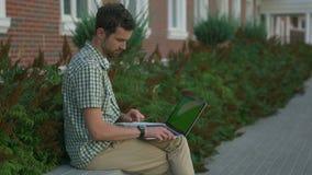 L'homme habillé occasionnel indépendant s'asseyent sur le banc et utilisent son smartwatch et ordinateur portable banque de vidéos